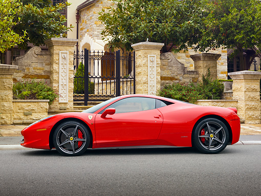FRR 04 RK0653 01 © Kimball Stock 2011 Ferrari 458 Italia Red Profile View On Pavement By Gate And Trees