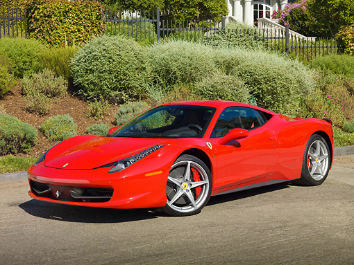 FRR 04 RK0658 01 © Kimball Stock 2011 Ferrari 458 Italia Red 3/4 Front View On Pavement By House And Shrubs