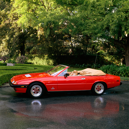 FRR 04 RK0140 07 © Kimball Stock 1982 Ferrari 400I Convertible Red Profile On Wet Pavement By Trees