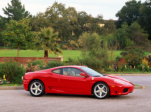FRR 04 RK0200 01 © Kimball Stock 1999 Ferrari 360 Modena Red Side 3/4 View Pavement With Trees And Shrubs