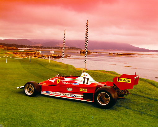 FRR 04 RK0352 05 © Kimball Stock 1977 Ferrari 312T2 Red 3/4 Rear View On Grass By Flags And Water
