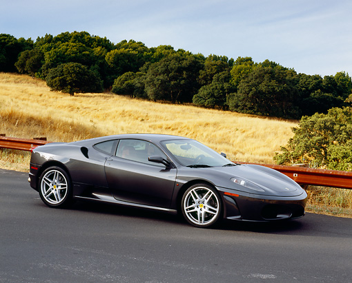 FRR 04 RK0383 04 © Kimball Stock 2005 Ferrari F430 Grigio Silverstone 3/4 Side View On Pavement Hill By Dry Grass Hills And Trees
