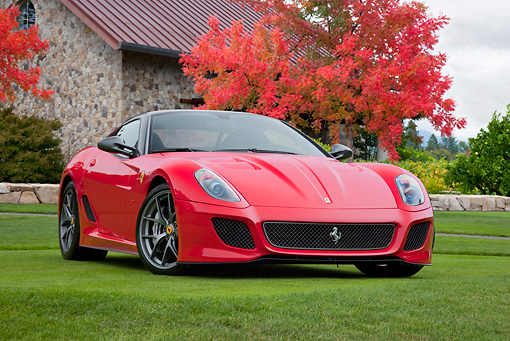 FRR 09 RK0059 01 © Kimball Stock 2011 Ferrari 599 GTO Red 3/4 Front View On Grass By Stone Building And Autumn Trees