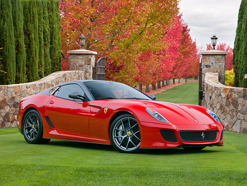 FRR 09 RK0060 01 © Kimball Stock 2011 Ferrari 599 GTO Red 3/4 Front View On Grass By Stone Gate And Autumn Trees