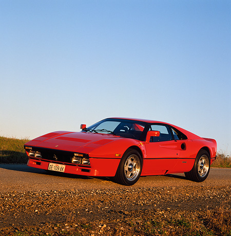FRR 14 RK0020 04 © Kimball Stock Red Ferrari 328 3/4 Front View On Dirt Road By Grass Blue Sky