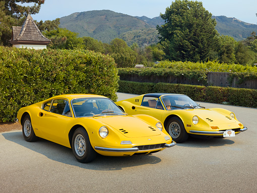 FRR 17 RK0007 01 © Kimball Stock 1969 Ferrari Dino 246 GT Coupe Yellow And 1973 Ferrari Dino 246 GTS Spyder Yellow 3/4 Front View On Pavement By Shrubs