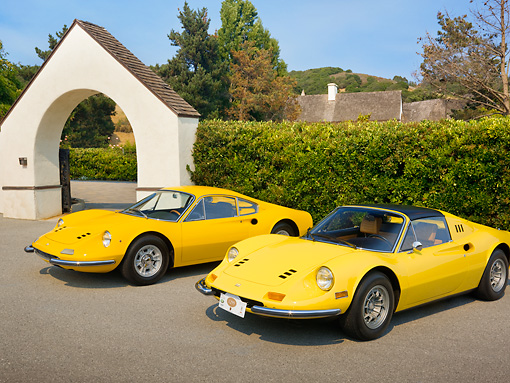 FRR 17 RK0008 01 © Kimball Stock 1969 Ferrari Dino 246 GT Coupe Yellow And 1973 Ferrari Dino 246 GTS Spyder Yellow 3/4 Front View On Pavement By Shrubs