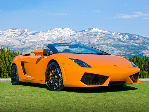 LAM 01 BK0014 01 © Kimball Stock 2010 Lamborghini Gallardo Spyder Orange 3/4 Front View On Grass By Snowy Mountain Range