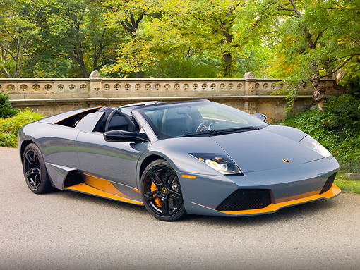 LAM 01 RK0752 01 © Kimball Stock 2010 Lamborghini Murcielago LP650 Roadster Gray And Orange 3/4 Front View On Pavement By Trees And Bridge