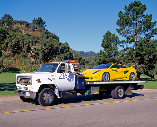 LAM 01 RK0016 01 © Kimball Stock Yellow Lamborghini Cala Italdesign On Tow Truck Driving On Road By Grass Blue Sky