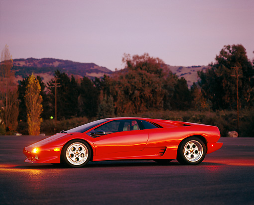 LAM 01 RK0063 02 © Kimball Stock Lamborghini Diablo Red Profile View On Pavement At Night By Trees
