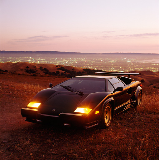 LAM 01 RK0072 08 © Kimball Stock Lamborghini Countach Black 3/4 Front View In Field At Dusk Above City Lights