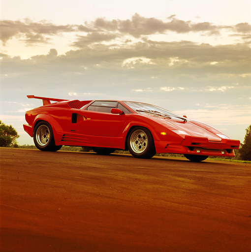 LAM 01 RK0160 02 © Kimball Stock 1989 Lamborghini Countach 25th Anniversary Red 3/4 Front View On Pavement Headlights On Sunset Clouds