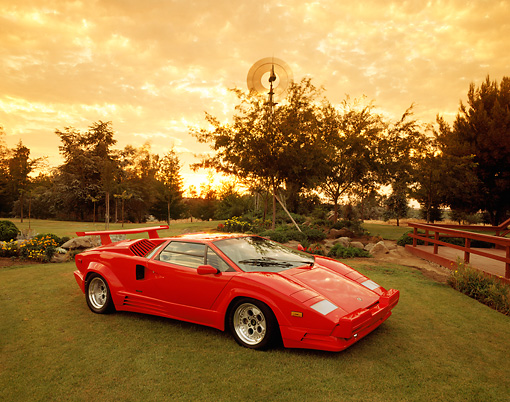 LAM 01 RK0171 01 © Kimball Stock 1989 Lamborghini Countach 25th Anniversary Red 3/4 Front View On Grass By Trees Clouds Sunset
