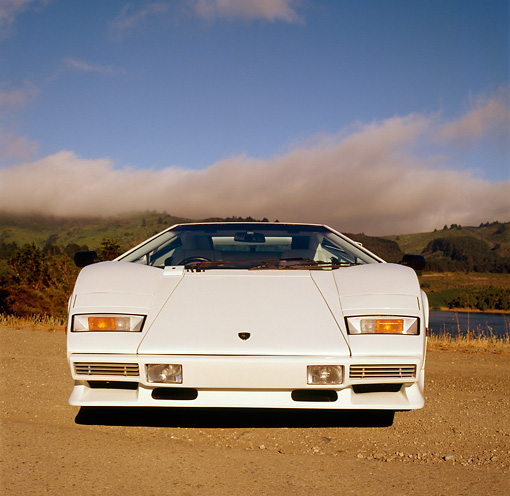 LAM 01 RK0174 06 © Kimball Stock Lamborghini Countach White Low Head On View On Dirt Blue Sky Clouds