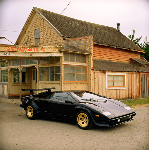 LAM 01 RK0214 01 © Kimball Stock Lamborghini Countach Black 3/4 Front View On Pavement By Old House