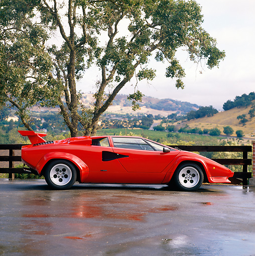 LAM 01 RK0407 02 © Kimball Stock Lamborghini Countach Red Side View On Wet Pavement By Tree Hills Background