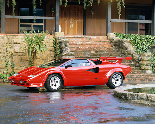LAM 01 RK0422 01 © Kimball Stock Lamborghini Countach Red 3/4 Side View On Driveway By Fountain And House