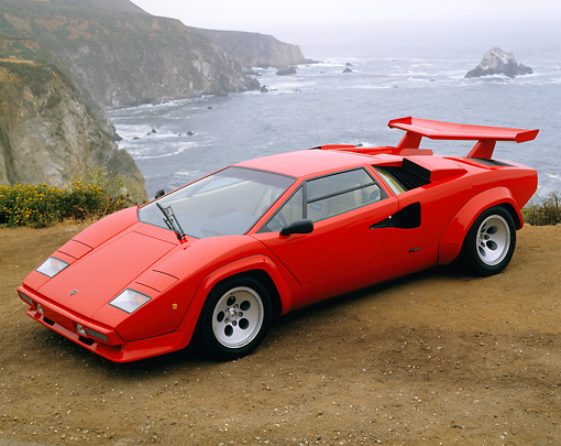 LAM 01 RK0426 04 © Kimball Stock Lamborghini Countach Red 3/4 Front View On Dirt Ocean And Rocks In Background Foggy