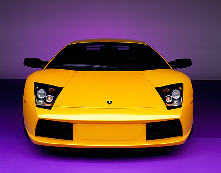 LAM 01 RK0449 02 © Kimball Stock 2002 Lamborghini Murcielago Yellow Head On Shot On Purple Floor Studio