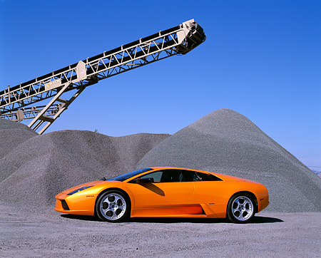LAM 01 RK0478 02 © Kimball Stock 2002 Lamborghini Murcielago Orange Low 3/4 Side View On Gravel By Crane Blue Sky