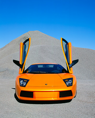 LAM 01 RK0481 11 © Kimball Stock 2002 Lamborghini Murcielago Orange Head  On Gravel Blue Sky
