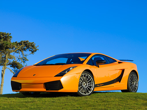 LAM 01 RK0634 01 © Kimball Stock 2007 Lamborghini Gallardo Superleggera Orange With Black Stripe Front 3/4 View On Grass Blue Sky