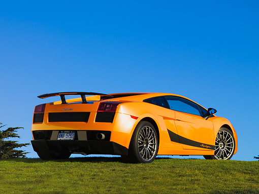 LAM 01 RK0635 01 © Kimball Stock 2007 Lamborghini Gallardo Superleggera Orange With Black Stripe Rear 3/4 View On Grass Blue Sky