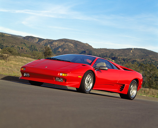 LAM 02 RK0076 21 © Kimball Stock 1991 Lamborghini Diablo Red Low 3/4 Side On Pavement Mountains And Blue Sky
