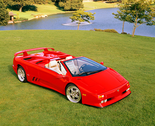 LAM 02 RK0103 10 © Kimball Stock 1995 Lamborghini Diablo Roadster 30th Anniversary Edition Red Overhead 3/4 Front View On Grass By Lake