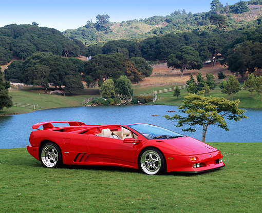 LAM 02 RK0106 02 © Kimball Stock 1995 Lamborghini Diablo Roadster 30th Anniversary Edition Red 3/4 Side View On Grass By Lake