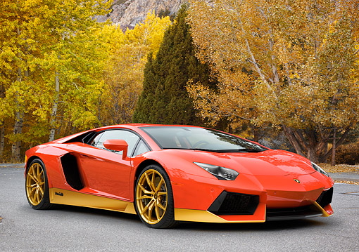 LAM 03 RK0030 01 © Kimball Stock 2016 Lamborghini Aventador Miura Homage 50th Anniversary Limited Edition Red And Gold 3/4 Front View On Road By Trees