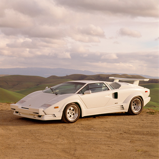 LAM 05 RK0005 07 © Kimball Stock Lamborghini Countach 25th Anniversary Edition White 3/4 Front View On Dirt By Mountains