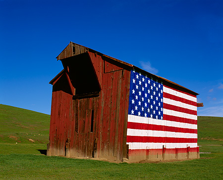 LAN 03 RK0028 08 © Kimball Stock Red Barn With American Flag On Side On Green Grass Blue Sky
