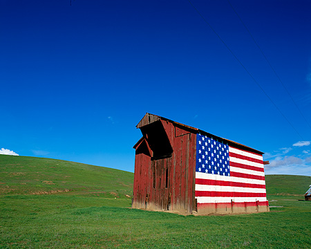 LAN 03 RK0028 11 © Kimball Stock Red Barn With American Flag On Side On Green Grass Blue Sky