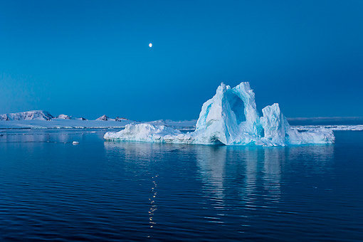 LAN 06 KH0015 01 © Kimball Stock Iceberg With Arches And Moon Above In Anarctica