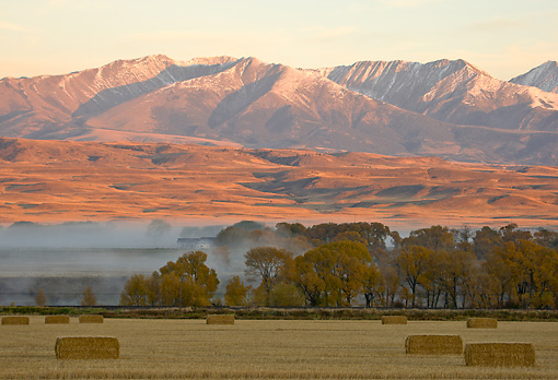 LAN 07 DS0009 01 © Kimball Stock Hay Bales In Farm With Mist And Mountains In Background In Montana