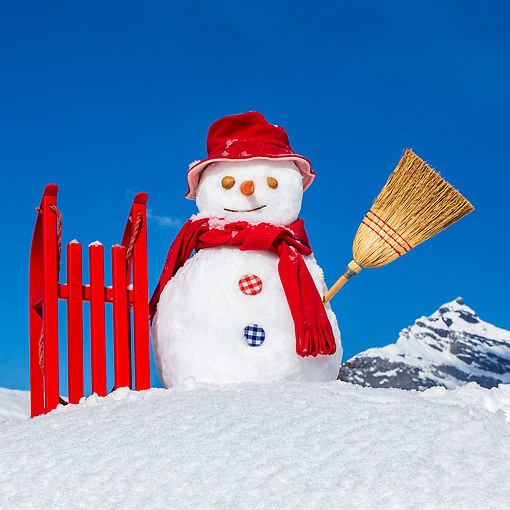 LAN 08 KH0126 01 © Kimball Stock Snowman By Red Sled Against Blue Sky
