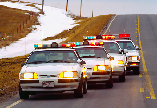 LAW 01 RK0004 01 © Kimball Stock Nebraska Police Cars In A Row On Road Lights On At Dusk