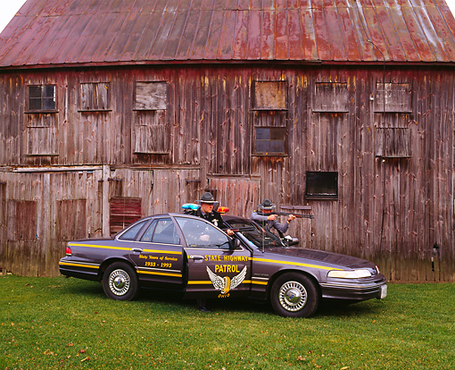 LAW 01 RK0009 03 © Kimball Stock 1994 Ford Crown Victoria Ohio State Highway Patrol Car And Officers Drawing Guns By Barn