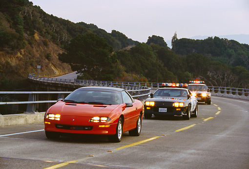 LAW 01 RK0020 01 © Kimball Stock California Highway Patrol Chasing Red Camaro On Highway