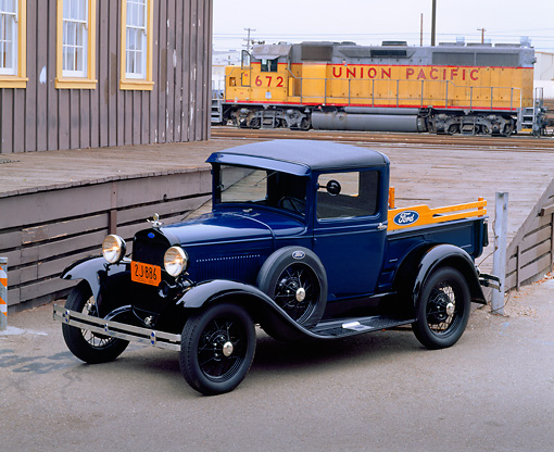 AUT 14 RK0447 01 © Kimball Stock 1930 Ford Model A Pickup Truck Blue 3/4 Front View On Pavement By Train