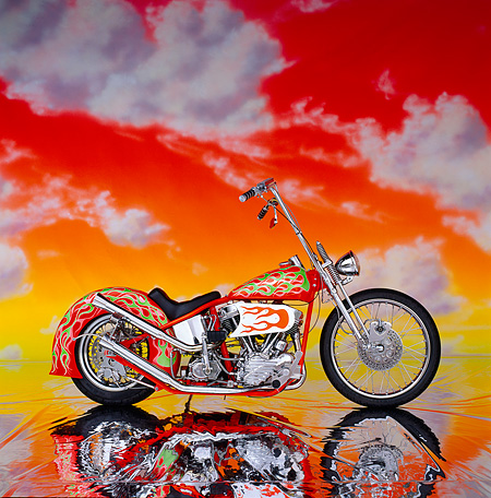 MOT 01 RK0080 03 © Kimball Stock Orange/green flames Custom Harley Davidson. profile in studio on glossy floor with orange sky and cloud background