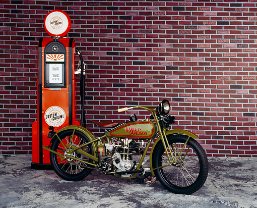 MOT 01 RK0084 02 © Kimball Stock 1926 Harley Davidson single cylinder racer, slight 3/4 front on mottled floor with brick wall and gas pump