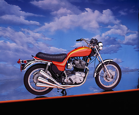 MOT 01 RK0330 01 © Kimball Stock 1973 Triumph Hurricane Orange 3/4 Side View On Orange Line Cloudy Blue Sky Background