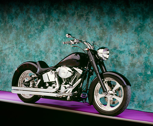 MOT 01 RK0602 04 © Kimball Stock 2000 Harley Davidson, Fat Boy, Black With Flames 3/4 Side View On Purple Floor Green Background Studio