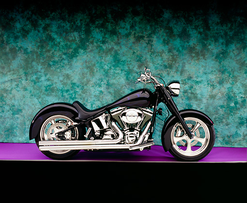 MOT 01 RK0603 03 © Kimball Stock 2000 Harley Davidson, Fat Boy, Black With Flames Profile View On Purple Floor Green Background Studio