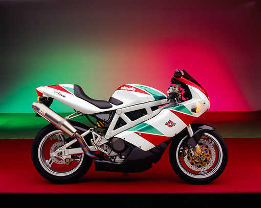 MOT 02 RK0163 01 © Kimball Stock 1999 Bimota DB4 Red Green And White Profile View On Red Floor Green And Red Lighting Studio