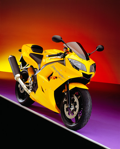 MOT 02 RK0269 08 © Kimball Stock 2005 Triumph Daytona 350 Yellow 3/4 Front View On Purple Floor Colorful Background Studio