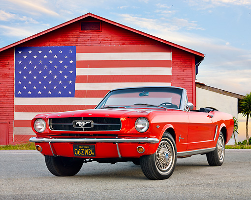 MST 01 BK0009 01 © Kimball Stock 1965 Ford Mustang Convertible Red 3/4 Front View On Gravel By Barn With American Flag